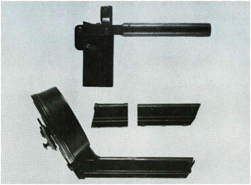 34.Conjunto carregador para 32 cartuchos onde se vê adaptador tampa de proteção e dispositivo com alavanca para auxiliar o processo de carregamento